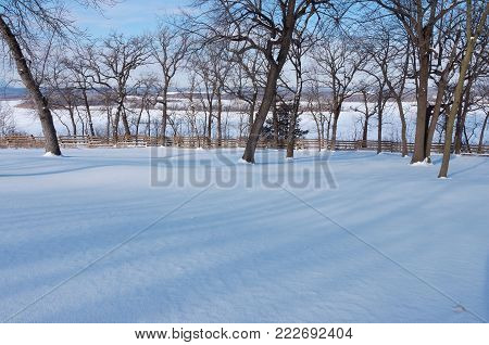 snow covered hilltop and frozen mississippi river below schaars bluff in spring lake regional park hastings minnesota