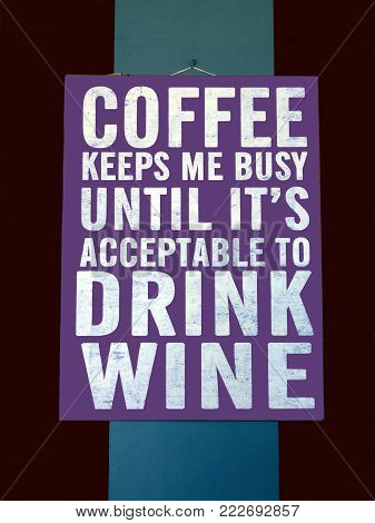 A Novelty Sign Suggesting That Coffee Will Keep You Busy Until Its Time To Drink Wine