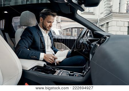 Checking the schedule. Handsome young man in full suit holding his personal organizer and looking at it while sitting inside of the car