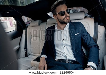 This is going to be a long day. Handsome young man in full suit looking away while sitting in the car