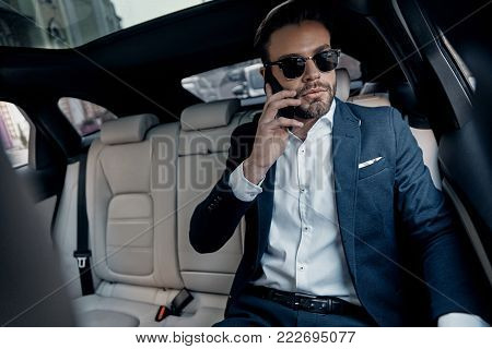 Discussing business details. Handsome young man in full suit talking on his smart phone while sitting in the car