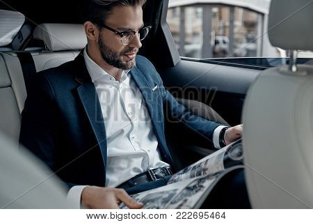 What is new in the world? Handsome young man in full suit reading a newspaper while sitting in the car