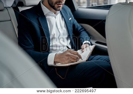 Young perfectionist. Close up of young man in formalwear writing something down while sitting in the car