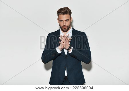 Confident in his style. Handsome young man in formalwear holding hands clasped and looking at camera while standing against grey background