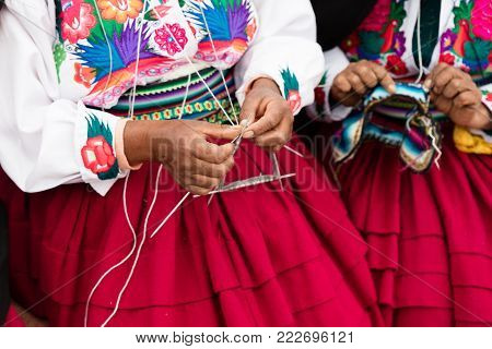 hands that sew typical costumes in Amantani on the Titicaca lake