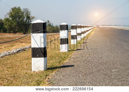 Milestones,black and white milestones with green grass roadside,lake roadside in background,concept for next step.go on