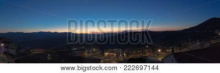 panoramic view of mountain silhouette, with small town in bottom, natural light tint blue, wild nature concept