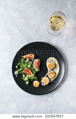 Fried scallops with lemon, figs, sauce and green salad served on ceramic black plate with glass of white wine over gray texture background. Top view, space. Plating, fine dining
