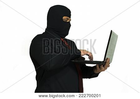 Hacker in the balaclava. In the hands of a laptop. Side view. computer crime