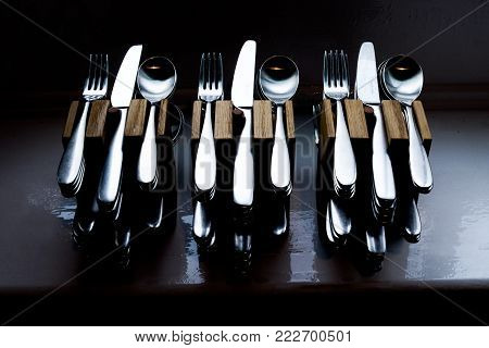 Twelve sets of beautifully lit quality cutlery, knives, forks, spoons in hand made wooden cutlery holders, they are stacked ontop of each other in patterns of three, silver cutlery on a grey black background