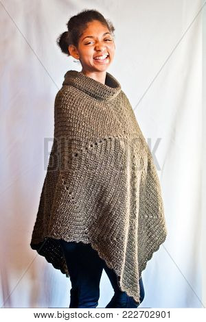 happy african american girl wrapped in warm poncho made by craftsman with knitting