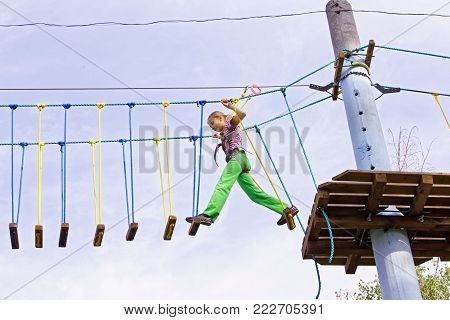 A teenage girl confidently moves on swinging boards at a height in a rope park. Courage and overcome