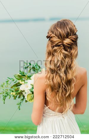 The bride is turned with her back and looks into the distance. Wedding flowers bouquet in bride's hand. Bride stands on the beach in wedding dress. Wedding day
