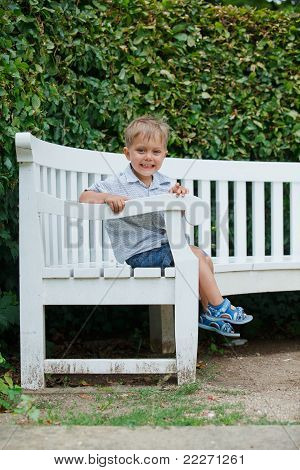 little boy sits on a bench in a park