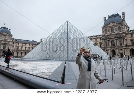 PARIS, FRANCE - DECEMBER 20, 2017: Tourist taking a selfie portrait in front of the Louvre Pyramid. Louvre pyramid (Pyramide du Louvre) is one of the main attractions of Paris, attracting a growing number of tourists