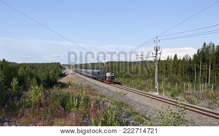 NORTH COUNTY, SWEDEN ON JULY 24. Long-distance train heading north on July 24, 2014 in North County, Sweden. Modern track through the countryside. Editorial use.