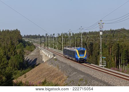 NORTH COUNTY, SWEDEN ON JULY 25. Intercity train heading north on July 25, 2014 in North County, Sweden. Modern track through the countryside. Editorial use.