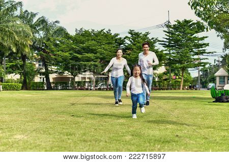 Concept Family.Parents and daughters go for a walk in the park.Family is doing holiday activities.