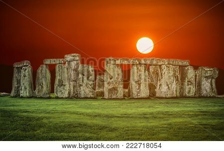 Stonehenge an ancient prehistoric stone monument at sunset in Wiltshire, UK.