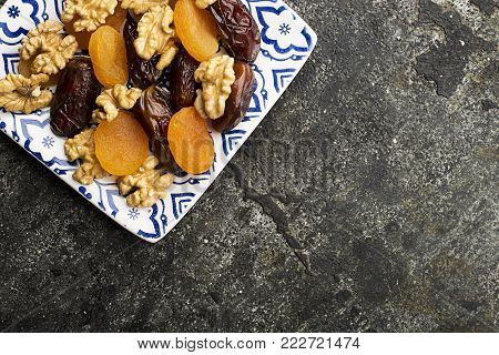 Blue white painted square plate full of walnuts and dried fruits: walnut, prunes, dates, dried apricots on a dark gray background. Top View