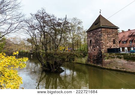 Autumn landscape with tree in the water of Pegnitz river and tower in cloudy weather. Nuremberg. Bavaria. Germany.