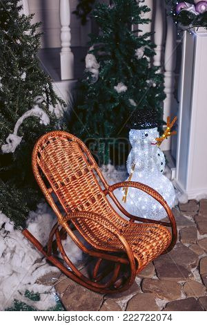 Wicker rattan chair, in a Christmas interior with a snowman and Christmas trees