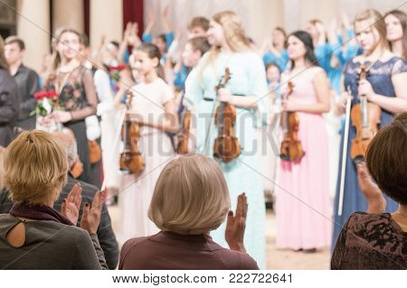 Spectators welcome musicians. string orchestra. selective focus