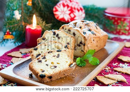 Sliced christmas fruitcake with raisins and mint leaf on christmas background. Colored horizontal indoors image.