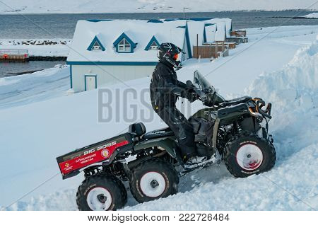 Hrisey Iceland - December 29. 2017: Member of the Icelandic Search and Rescue Association driving an ATV in snow during winter