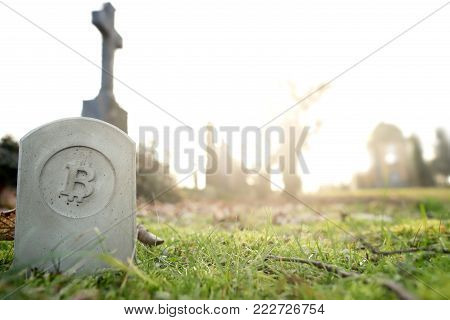 stone monument/tombstone with bitcoin symbol standing in green grass on cementery in front of stone cross - wide angle view - sunny blurred background with space for text - economic/financial concept
