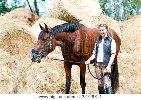Young teenage smiling girl owner standing with her beautiful bay horse at farm yard on yellow hay/straw rolled stack background looking at camera. Vibrant colored outdoors horizontal summertime image.