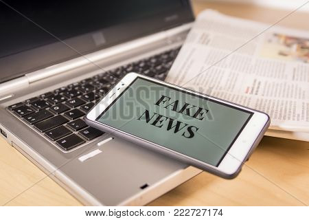 Smartphone with Fake News words on screen over a newspaper and a laptop. HOAX and Fake news concept.