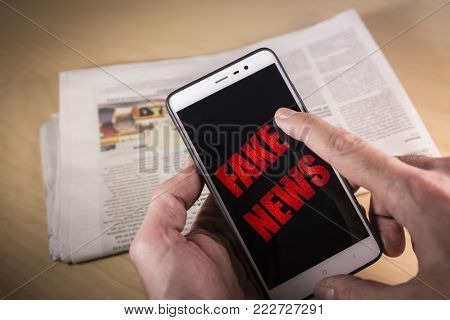 Hand holding a Smartphone with red Fake News words on screen and a newspaper on the background HOAX and Fake news concept.
