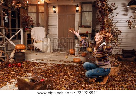 Beautiful young happy brown-haired woman, dressed in sweater, jeans and yellow shoes, tossing dry fall leaves up near the porch steps in autumn time. Courtyard, lit by flashlights, with pumpkins.