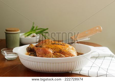 Baked chicken with herbs and garlic, served with sour cream sauce and dill. Rustic style, selective focus.