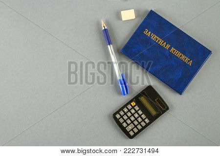 A blue book with an inscription in Russian - a student's record book. Pen, calculator on a gray background. Students' Day. Copy space