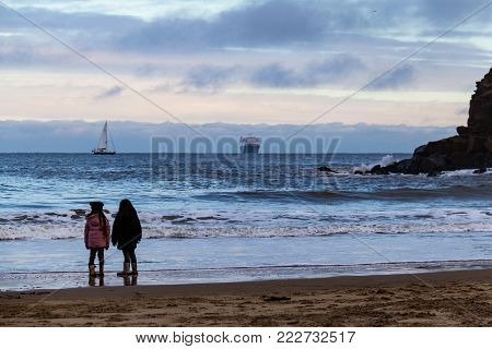 Girl Gazing At The Rough Sea And Ferryboat, Tynemouth, Uk