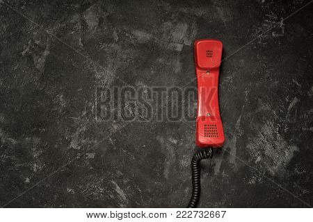 Red retro styled phone handset and black cement background