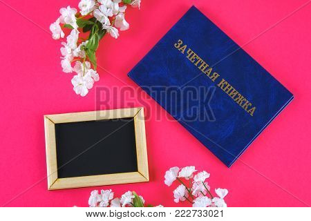 A blue book with an inscription in Russian - a student's record book. White flowers on a pink background. Students' Day. Tatyana's Day. Copy the space