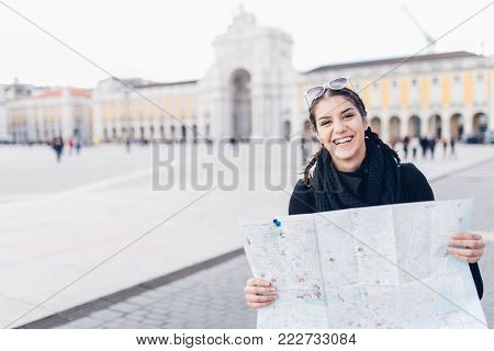 Cheerful female traveler on a trip to Europe.Female tourist holding a map in her hands,sightseeing landmarks around capital of Portugal.Exited woman standing on main Commerce square in Lisbon