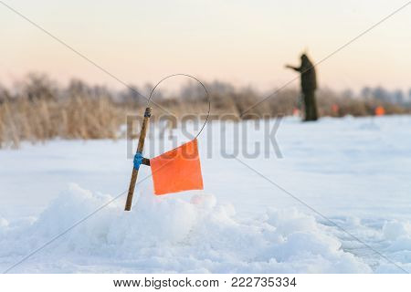 Winter fishing rod and ice hole close up, tip-up with reel and orange flag tackle
