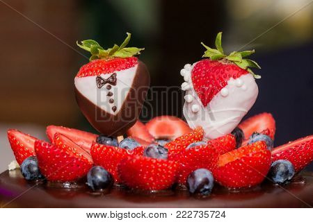 Strawberry bridal couple bride groom at luxury wedding drip cake. Confectionery art trend with marriage strawberries man woman embellishment, chocolate, blueberries and frosting cream. Symbol of love.