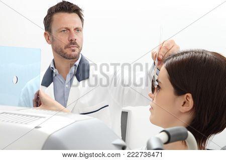 optometrist examining eyesight, woman patient pointing at the hole on plexiglass, isolated on white, ocular dominance test