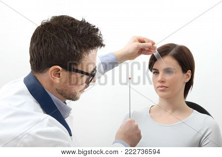 optometrist examining eyesight, woman patient pointing at the sphere, Nsuco saccadic movements test