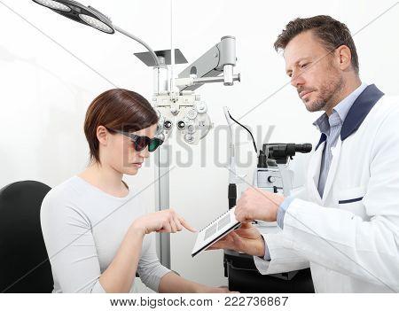 optometrist examining eyesight  woman patient in optician office, stereo test