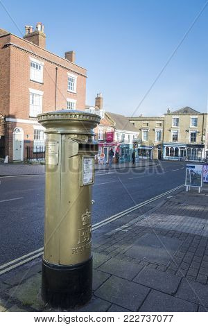 LYMINGTON, NEW FOREST, HAMPSHIRE, UK, JANUARY 2018 - A postbox in Lymington High Street, painted in gold to celebrate Ben Ainslie, gold medal winner in the London 2012 Olympic Games