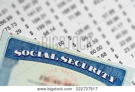Social Security card in the USA laid on top of figures and calculation of budget in retirement