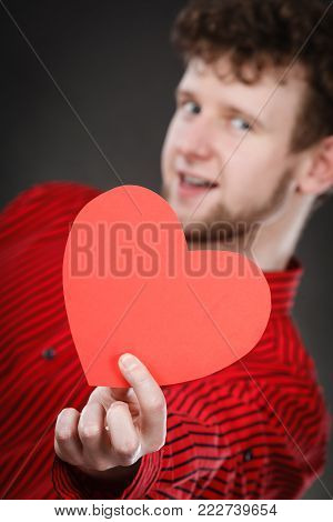 Feelings affection happiness concept. Cheerful man holding heart. Youthful energetic smiling male holding love symbol cutout.