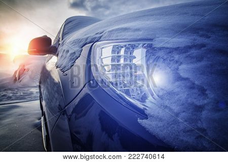 part of the car with snow and a glowing lamp in the headlight
