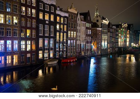 River channel and houses in Amsterdam, Netherlands. Night city view. Vacation, travel, journey concept
